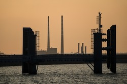 Beautiful telephoto view Poolbeg CCGT chimneys and Pigeon House Powers Station between wingwalls of St Michael pier ferry terminal in Dun Laoghaire harbor, Dublin, Ireland. Soft and selective focus