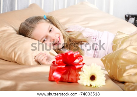 beautiful ten years' girl has seen in bed a gift on birthday.