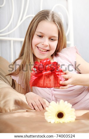 beautiful ten years\' girl has seen in bed a gift on birthday.