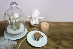 beautiful tender stilllife, snowdrop, Galanthus in vase, candle, small cup of coffee, cappuccino, concept of coffeetime, romantic spring morning, floral spring background