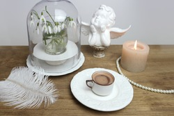 beautiful tender stilllife, snowdrop, Galanthus in vase, small cup of coffee, cappuccino, concept of coffeetime, romantic spring morning, floral spring background