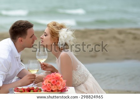 Beautiful tender wedding couple of young man and woman sitting on ocean beach shore at table with rose bouquet red strawberry kissing and drinking white wine from glasses copyspace, horizontal picture