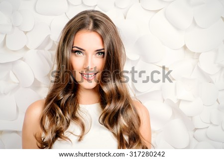 Beautiful tender woman in white dress posing by the background of white paper flowers. Beauty, fashion. Haircare. Cosmetics.