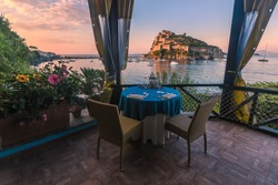 Beautiful terrace for a romantic dinner overlooking the Aragonese castle. Ischia. Italy