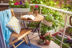 Beautiful terrace or balcony with small table, chair and flowers