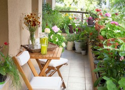 Beautiful terrace or balcony with small table, chair and flowers. Summer time Idyllic seating in the terrace with drink.