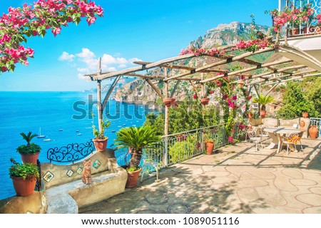 beautiful terrace with table, chairs and blooming flowers with view of sea and mountains near Positano, Amalfi coast, Italy