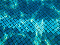 Beautiful texture of a small square ceramic tile with seams in a pool under blue water, underwater view in the pool, sea, ocean in a tropical seaside resort. The background.