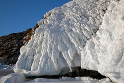 Beautiful textured frozen formations of white ice on mountain rock, formed by waves and extremely cold temperature, scenic winter landscape