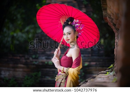 Beautiful Thai girl in traditional dress costume red umbrella as Thai temple where is the public place, Thai Woman in Traditional Costume of Thailand.