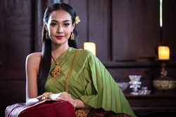 Beautiful Thai woman in traditional costume in ancient home