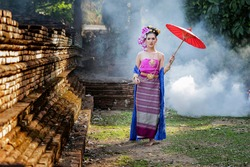 Beautiful Thai woman wearing thai traditional clothing with red umbrella in amid the smoke and fog.
