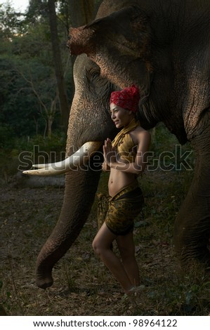 Beautiful Thailand model making traditional polite pose standing with massive friendly Asian elephant in jungle scene photographed with studio strobe in nature park.
