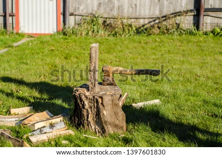 Beautiful thing and thing. Beautiful view and background on the stump, on which stands a vertically wooden log or log and an ax, in the fresh air in the village during the day and summer. #1397601830