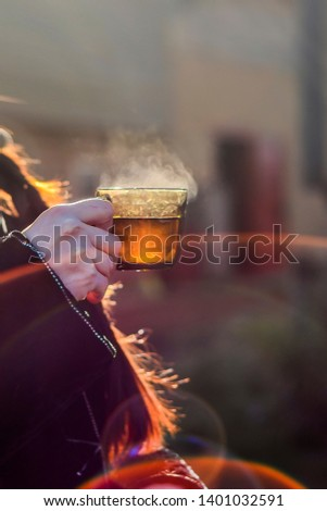 Beautiful thing and thing. Beautiful view of a glass of hot tea with steam, in the hands of man, in nature and sunset. #1401032591