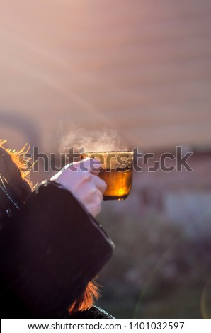 Beautiful thing and thing. Beautiful view of a glass of hot tea with steam, in the hands of man, in nature and sunset. #1401032597