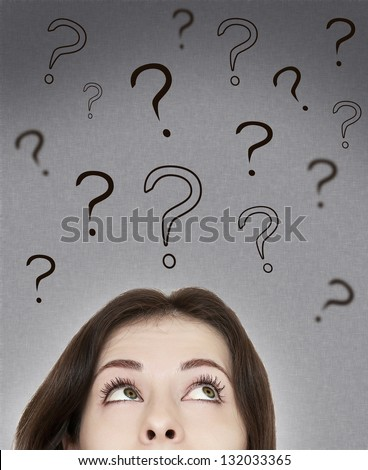 Beautiful thinking woman looking on questions marks above her head on grey background