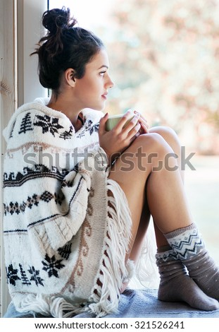 Beautiful thoughtful brunette woman with cup of coffee wearing knitted nordic print poncho sitting home by the window. Blurred garden fall background.