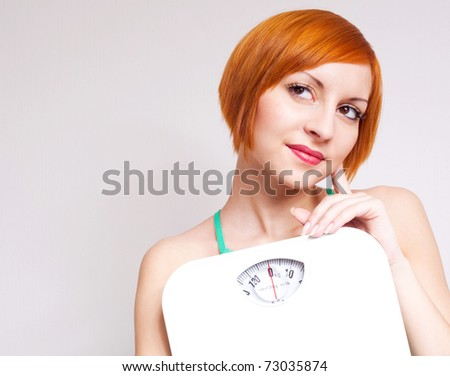 beautiful thoughtful young sporty woman  holding scales