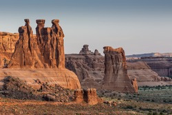 Beautiful Three Gossips rock formation lit by the rising sun on an early morning at Arches National Park near Moab Utah.