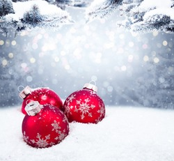 Beautiful three red Christmas balls on the red background. Christmas ornament on snow with fir branches.