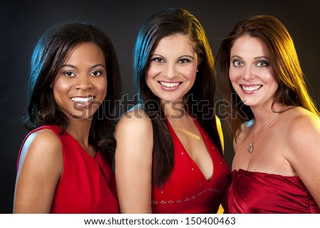 beautiful three women having fun during party on dark background