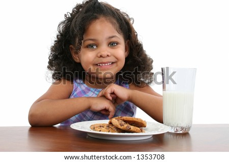 Beautiful three-year-old African American girl drinking milk and eating cookies.
