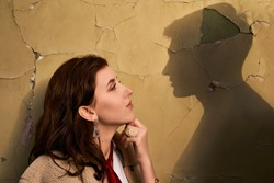 Beautiful througtful young woman thinks of her ideal boyfriend man or lover represented by a shadow on the wall.