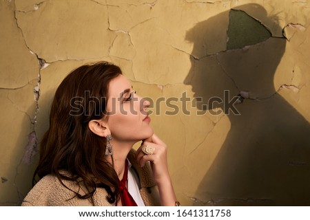 Photo of  Beautiful througtful young woman thinks of her ideal boyfriend man or lover represented by a shadow on the wall.