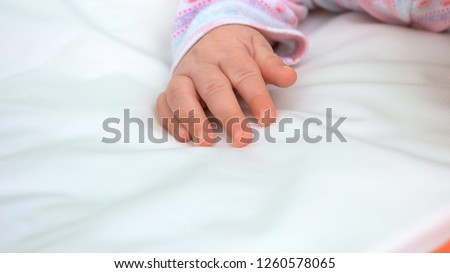 Beautiful tiny hand of infant girl. Infant kid on white blanket, cropped image. Beauty and softness of newborn skin. New life concept. Infant baby care tips.
