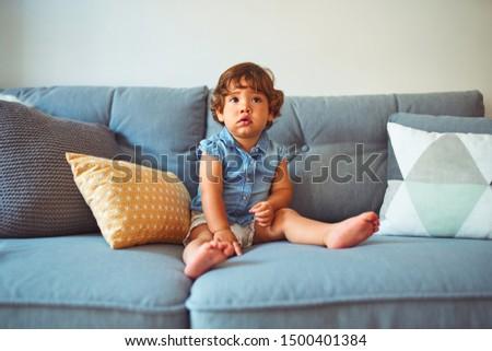 Beautiful toddler child girl wearing blue denim shirt sitting on the sofa
