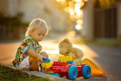 Beautiful toddler child, playing with plastic toys, blocks, cars on sunset in a small village