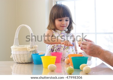 Beautiful toddler girl coloring eggs for Easter holiday