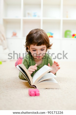 Beautiful toddler girl reading a book on the carpet