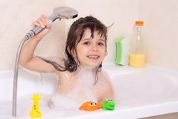Beautiful toddler girl taking a bath in a bathtub with bubbles. Cute kid washing his hair with shampoo in the shower.