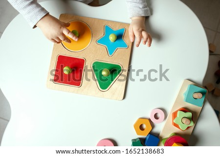 Beautiful toddler play with a wooden frame puzzle geometric figure toys at home. Toddler play with a color educational toy.  Child development.  Baby hands. View from above. Detail