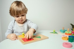 Beautiful toddler play with a wooden toys at home. Toddler play with a color educational toy.  Child play at the table in the baby room. Child development.  Funny baby. Lifestyle.