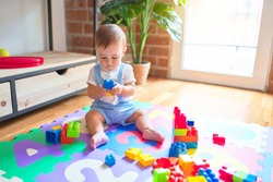 Beautiful toddler sitting on puzzle carpet playing with building blocks at kindergarten