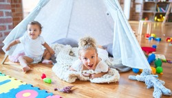 Beautiful toddlers playing inside tipi over blanket around lots of toys at kindergarten