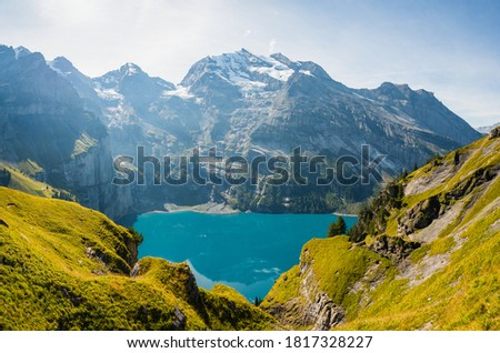 Photo of  Beautiful top view of Oeschinensee, Oeschinen Lake by Kandersteg, Switzerland.  Scenic image of most popular tourist attraction. Discover the beauty of earth. Sunny summer day,