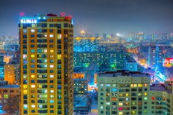 Beautiful top view of the city. Colorful street lighting of the night metropolis. Many high-rise buildings. Cold winter weather. There is snow on the roofs of houses. Novosibirsk, Siberia, Russia.