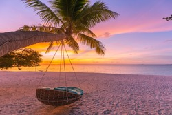 Beautiful tourism landscape, holiday island coast. Luxury summer vacation concept, swing or hammock on amazing palm tree near the sea. Colorful sunset landscape, perfect beach view. Amazing beach