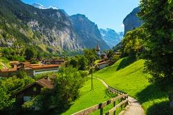 Beautiful tourist alpine village in the spectacular deep valley. Fantastic travel and touristic destination, Lauterbrunnen village with glaciers in background, Bernese Oberland, Switzerland, Europe