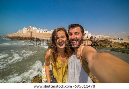 Beautiful tourist couple smiling and taking photo selfie with Cityscape of Essaouira, a UNESCO world heritage site in Morocco. North Africa #695811478