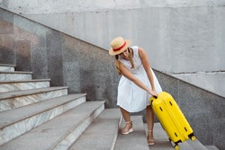 Beautiful tourist girl travels. Pulls a large yellow suitcase up the steps. Heavy load.