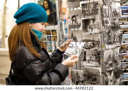 Beautiful tourist in Paris choosing souvenir postcards
