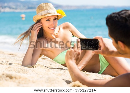 Beautiful tourist woman has asked a local man to take a photo of her lying on a beach sand with her smartphone #395127214