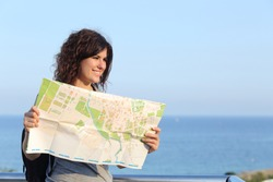 Beautiful tourist woman on vacation with a city map with the sea and sky in the background