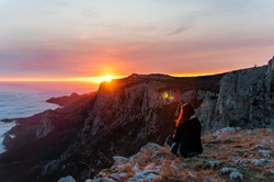 Beautiful tourist woman sitting on a rock high in the mountains, above the clouds and enjoying the sunset Copy space. The concept of calmness, silence and unity with nature