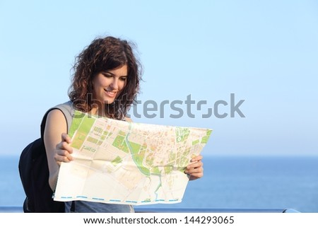 Beautiful tourist woman watching a city map with the sea and the sky in the background